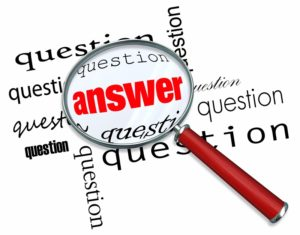 A magnifying glass hovering over many questions to find the answ